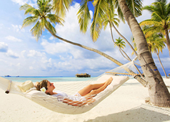 Photo of a woman in a hammock on the beach, for information on sedation dentistry from Lowell MA dentist Dr. Michael Szarek.