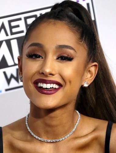Head-and-shoulders photo of Ariana Grande smiling. Her hair is in a ponytail, she is wearing diamond earrings, a diamond necklace and a black spaghetti-strap top or dress; for information on cosmetic dentistry and smile makeovers from Dr. Michael Szarek an accredited cosmetic dentist in Massachusetts.