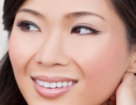 Asian woman smiling - for info on dental crowns on healthy teeth from Lowell, MA dentist Dr. Szarek